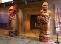 Woodcarvings by Joe Gobin and James Madison stand at a gallery entrance.
