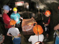 Headlamps provide the only light during an underground mine tour.
