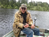 Bob Ellsberg's fishing companion, Milford, clutches a trophy fish.