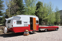 A 1961 Ford Galaxie Sunliner convertible tows a 1962 Shasta travel trailer.