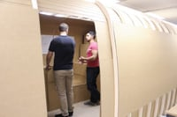 Students exchange design ideas inside a plywood model of an Airstream shell.
