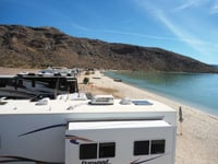 Travel trailers and motorhomes line the beach at Playa Santispac.