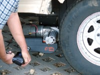 A socket-driving drill is used to disengage the trailer mover from the tire.