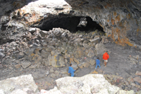 A trail leads visitors to a cave at Craters of the Moon.