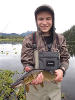 Tanis Miller, whose father, Bob Miller, owns a fly-fishing shop in Alaska, displays pike caught near Yakutat.