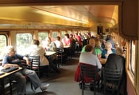 Passengers sit at tables during a scenic rail trip.