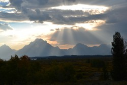 The Tetons lit by shafts of light at sunset.