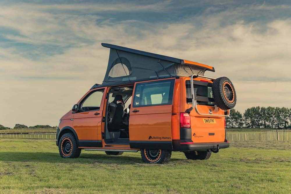 An overlanding camper van with pop top raised.