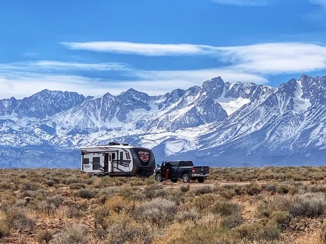 travel trailer and truck with mountains in background.