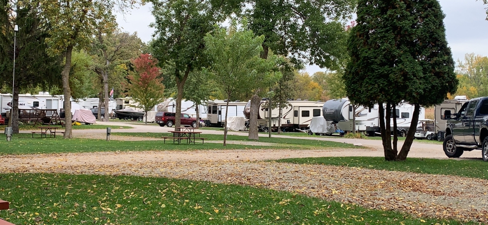 Medium shot of RV park with grass and trees in the foreground and RVs in the background. - camping in Minnesota