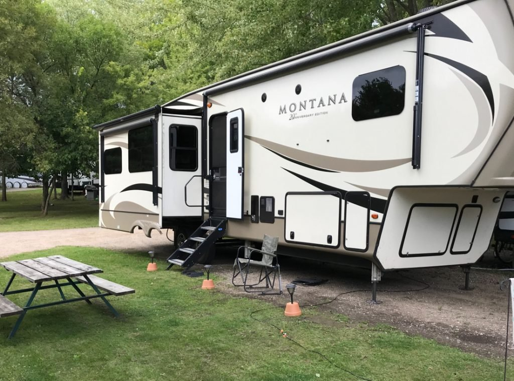 Montana fifth wheel RV parked with green grass and picnic table