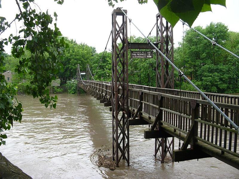 Long swinging walking bridge over a river.