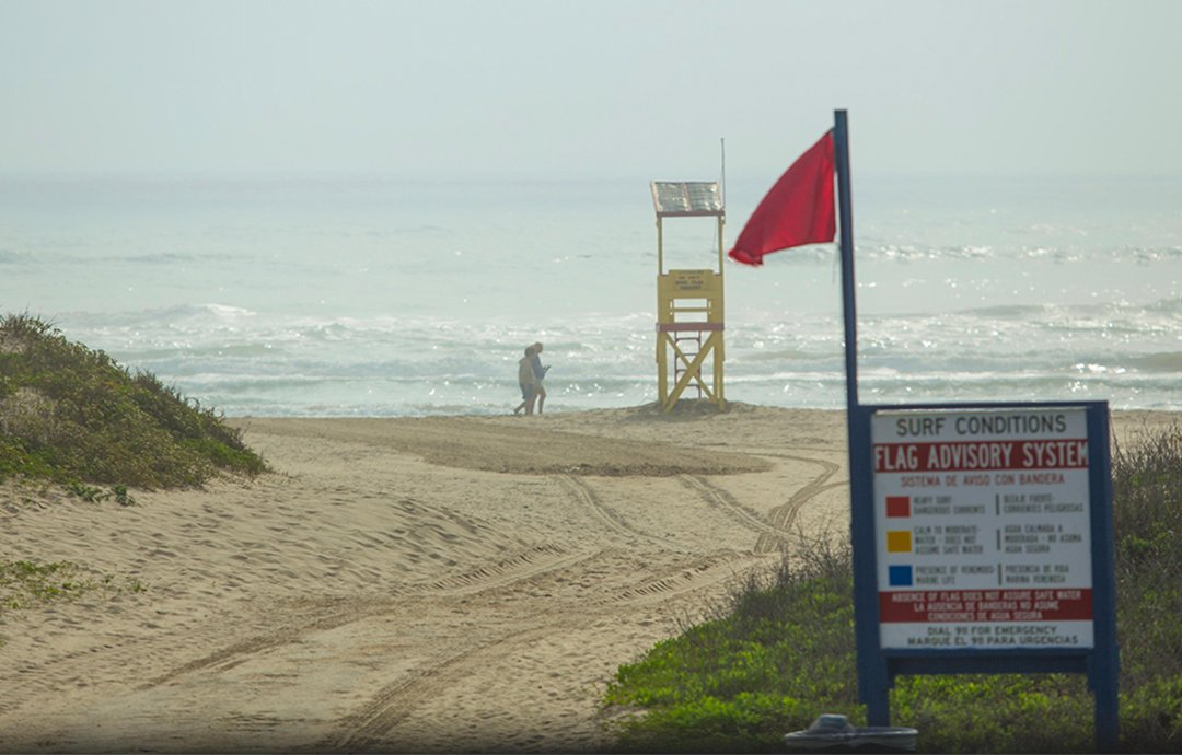 Beach with red flag and flag advisory sign in Texas