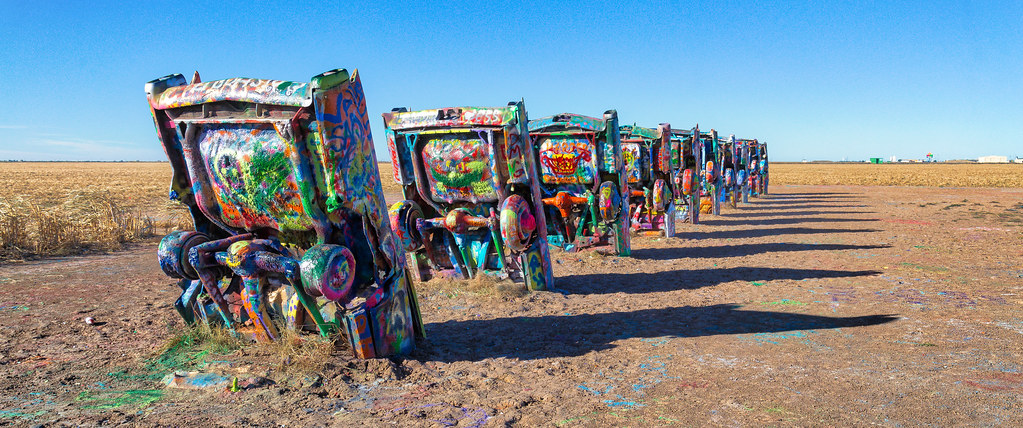 Colorful cars covered in graffiti buried front end first.