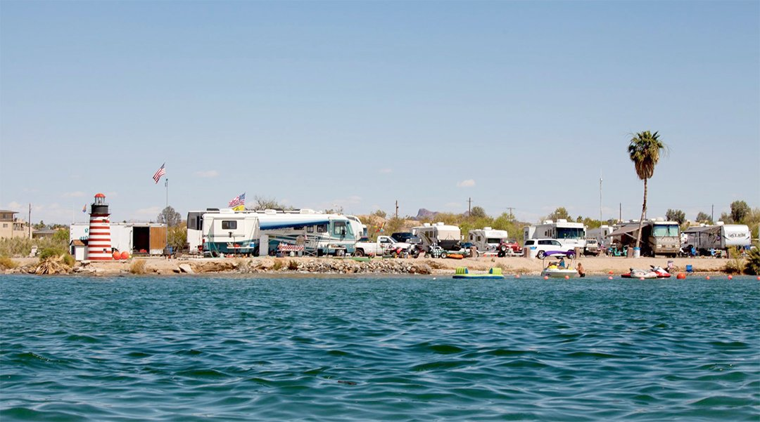 RVs and vehicles on the beach of Lake Havasu with water in the foreground