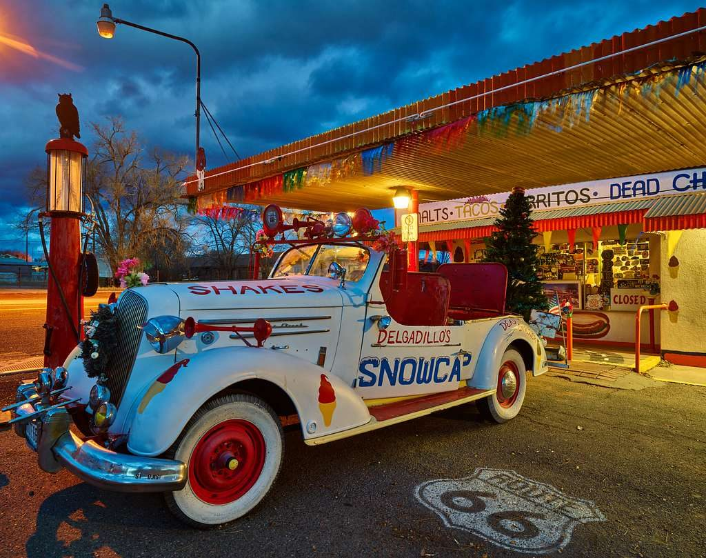 Antique white car in front of a colorful drive in restaurant.