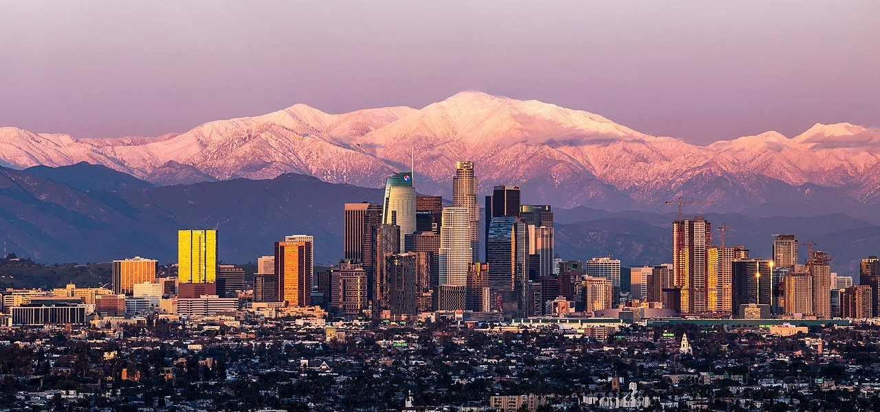 Skyline of Los Angeles, California with snow-capped mountain in background.