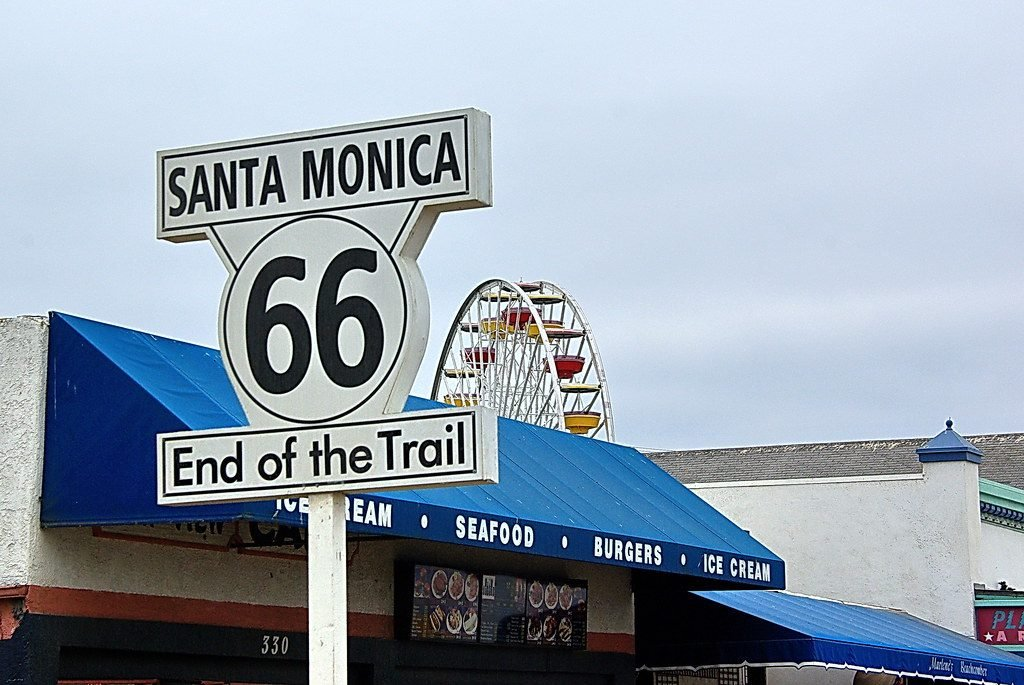 Santa Monica Route 66 End of the Trail sign with Ferris wheel in the background.