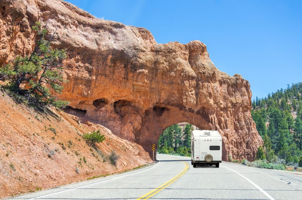 RV driving in Utah entering arch over highway.