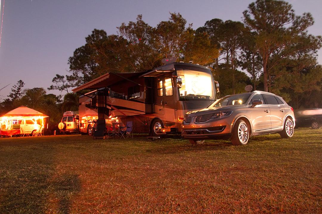 RV and car at an RV park at night
