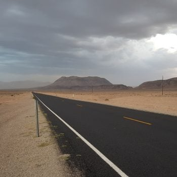 driving through death valley with storm clouds in sky