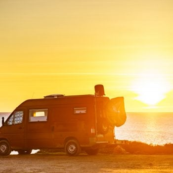 Camper van on the beach at sunset.