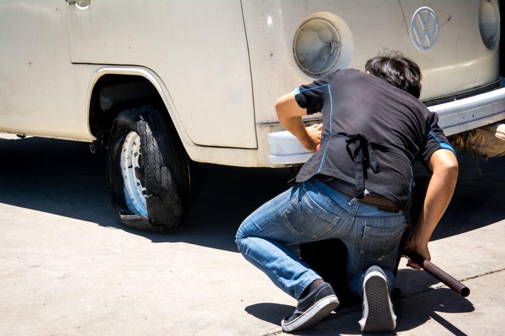 VW camper van getting tire changed.