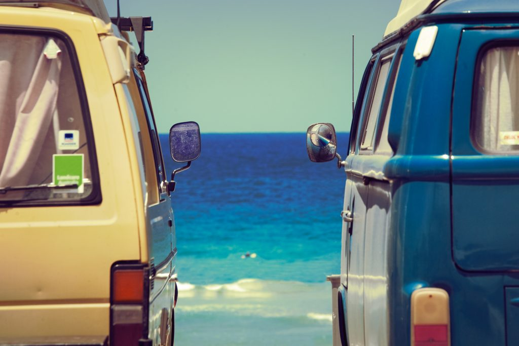 Camper vans parked near ocean shore.