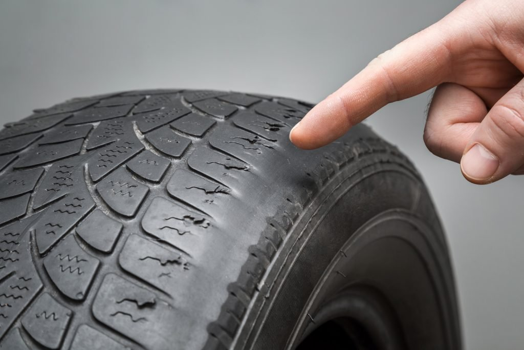 Finger points to uneven tread wear on a tire.