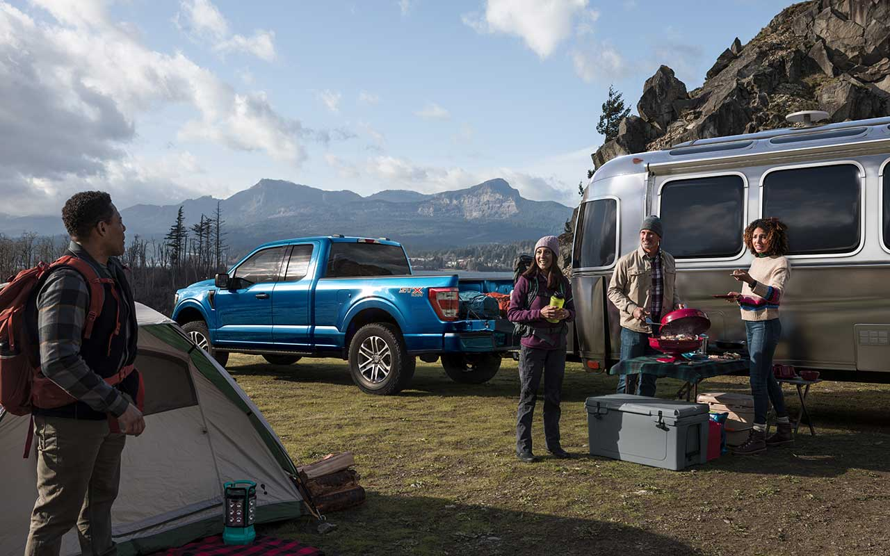 Blue Ford F150 pickup truck with Airstream travel trailer and four young campers