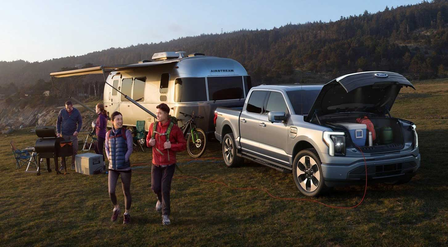 Ford F150 Lightning and Airstream trailer with family camping