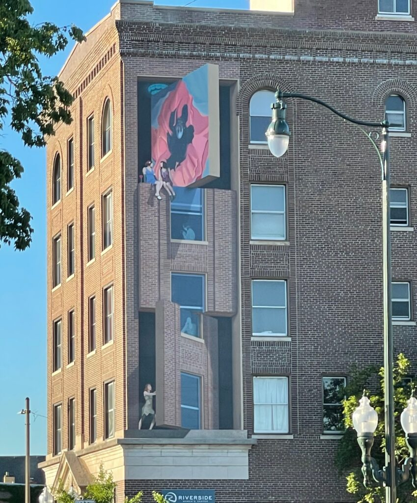 a four story mural that makes the building look like it's being opened up