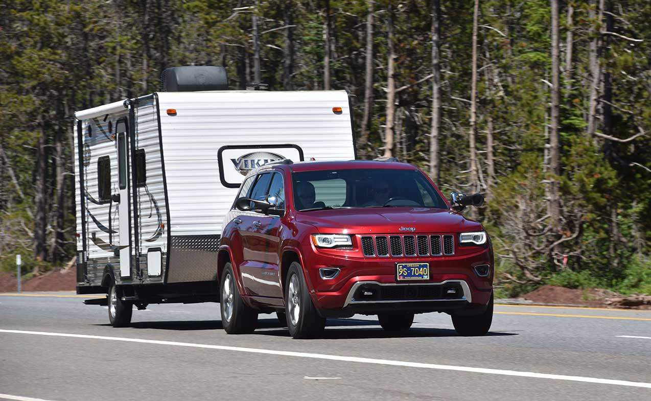 Red Jeep Grand Cherokee on highway towing Viking travel trailer