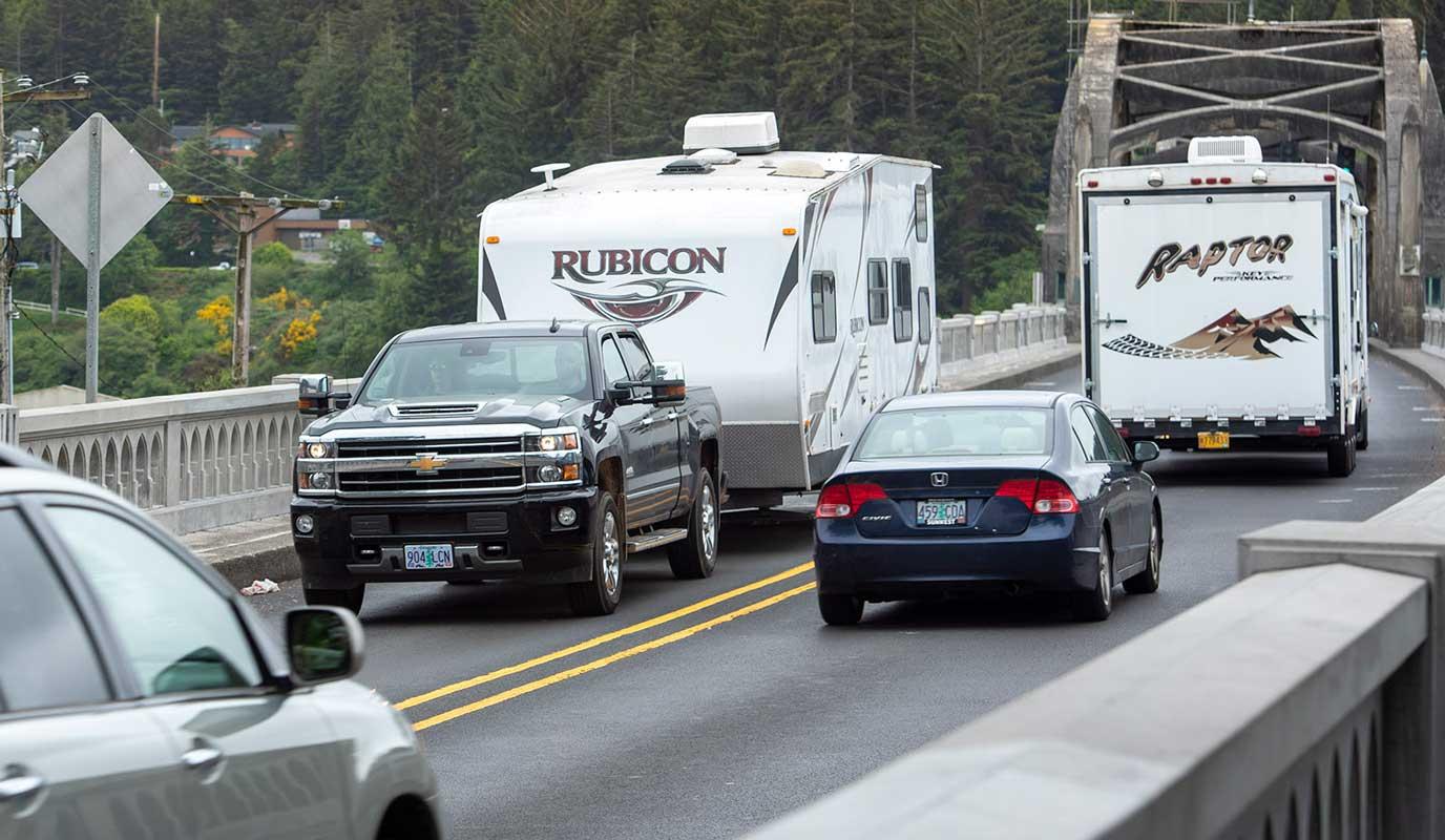 RV trailers on bridge being towed by pickup trucks