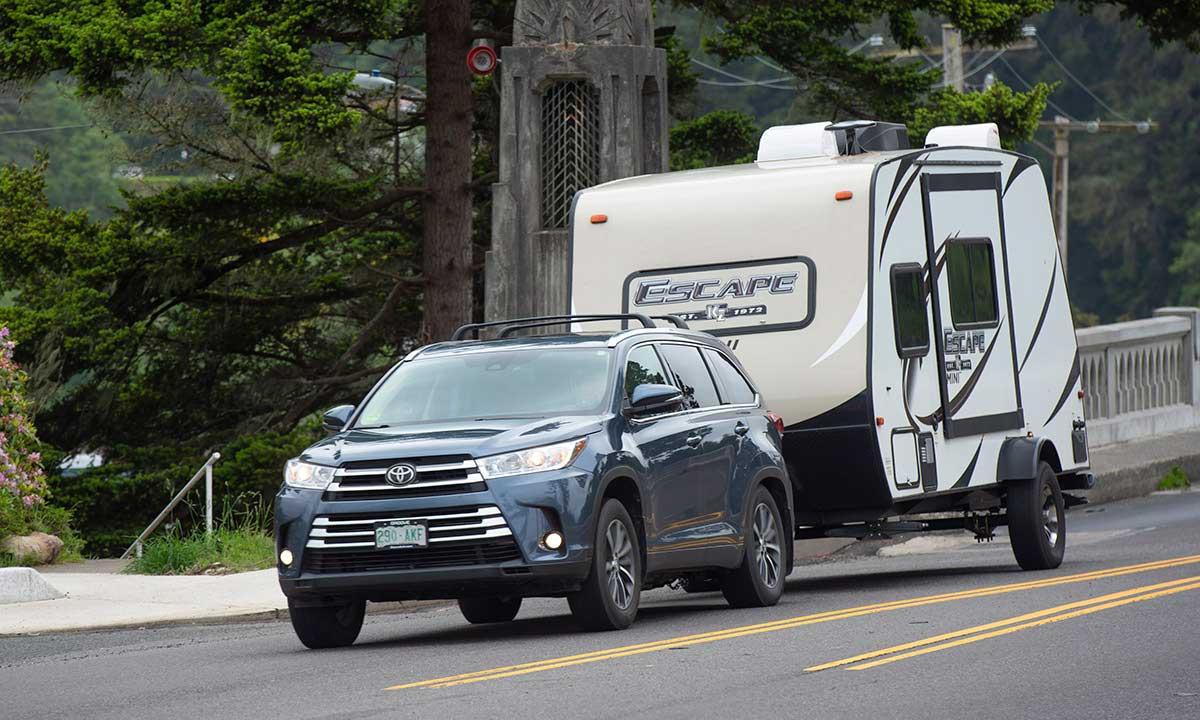 Toyota Highlander SUV towing Escape travel trailer on highway