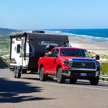 Red Toyota Tundra pickup truck towing a travel trailer near ocean