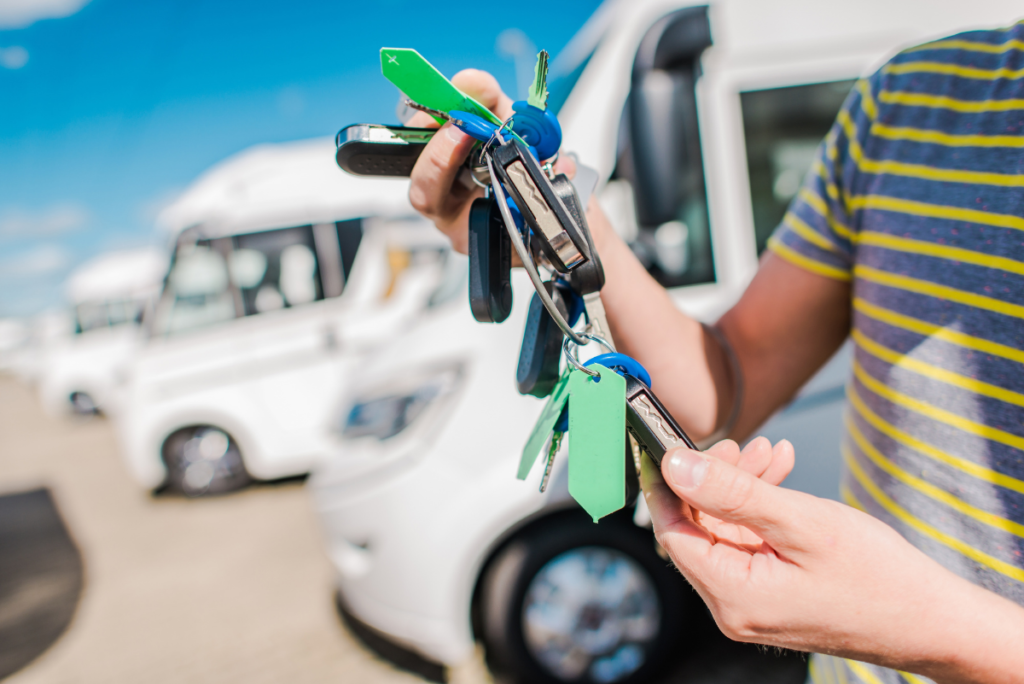 Person holding keys beside row of RVs - used RV
