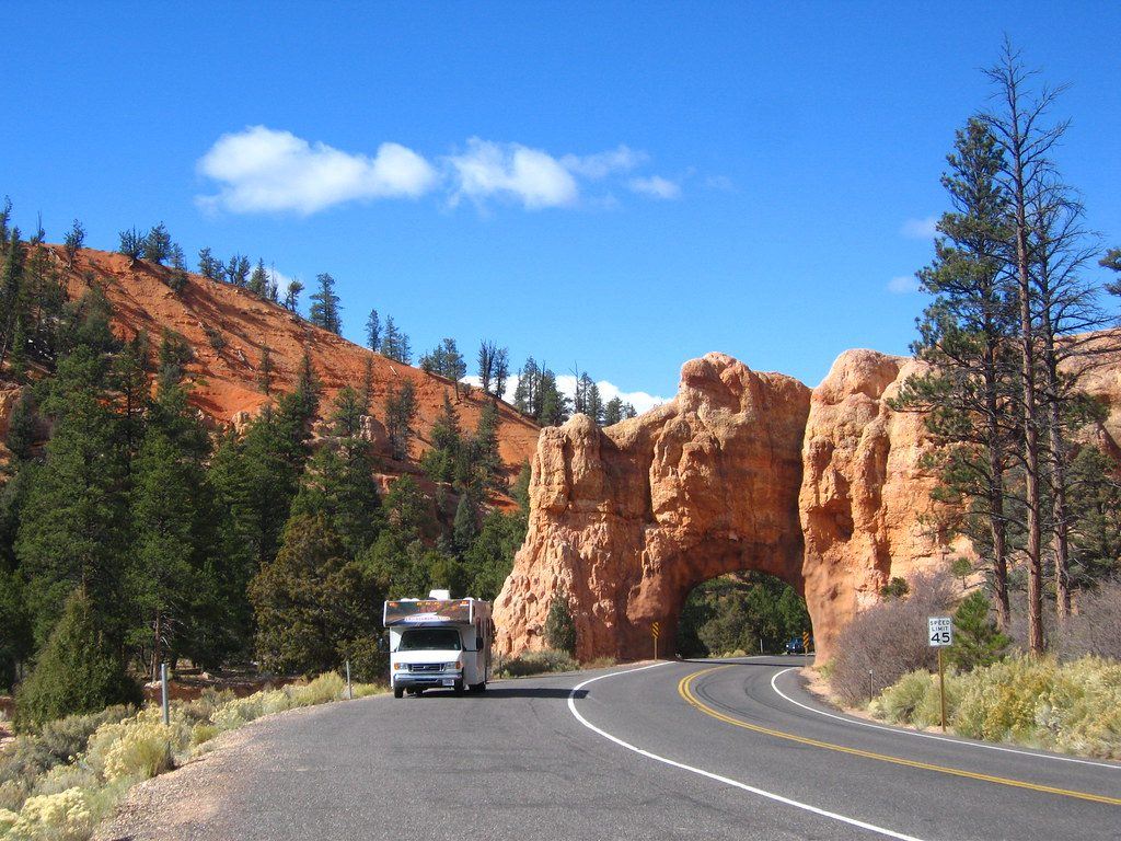 Red cliffs towering above an RV with blue sky and trees - is RV life for me