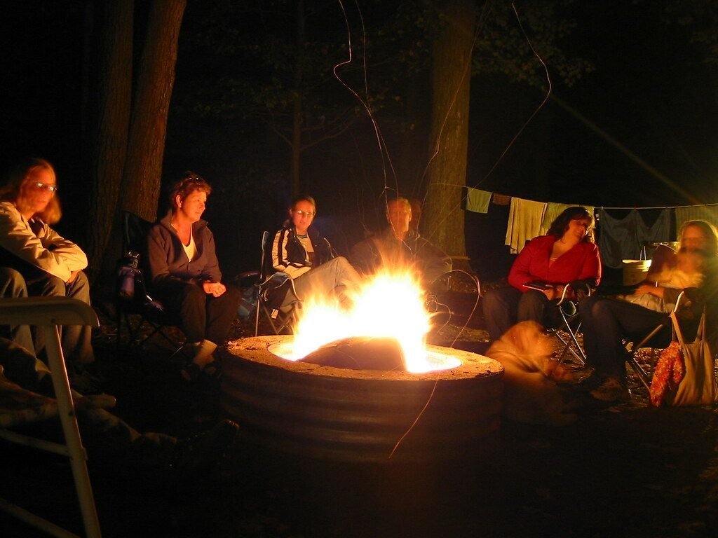 Group of people sitting around a bonfire