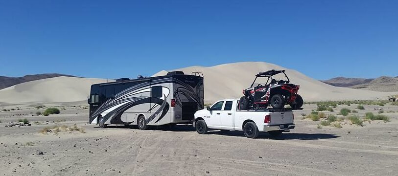 Class A RV towing a white pickup truck with four-wheeler in the bed - RV tow bars