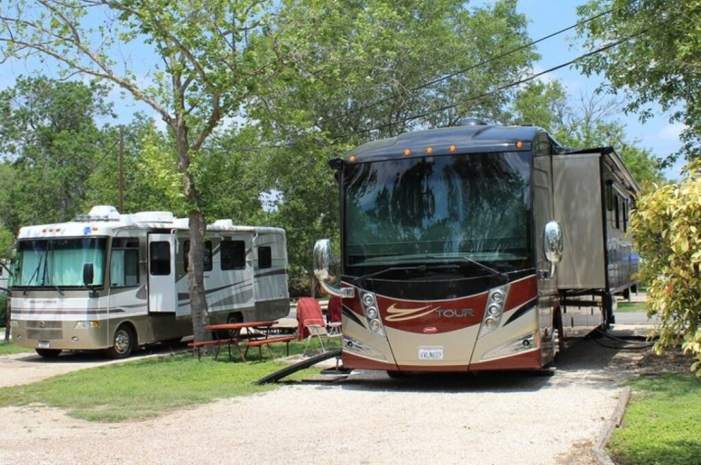 Two RVs parked in sites with trees and blue sky.