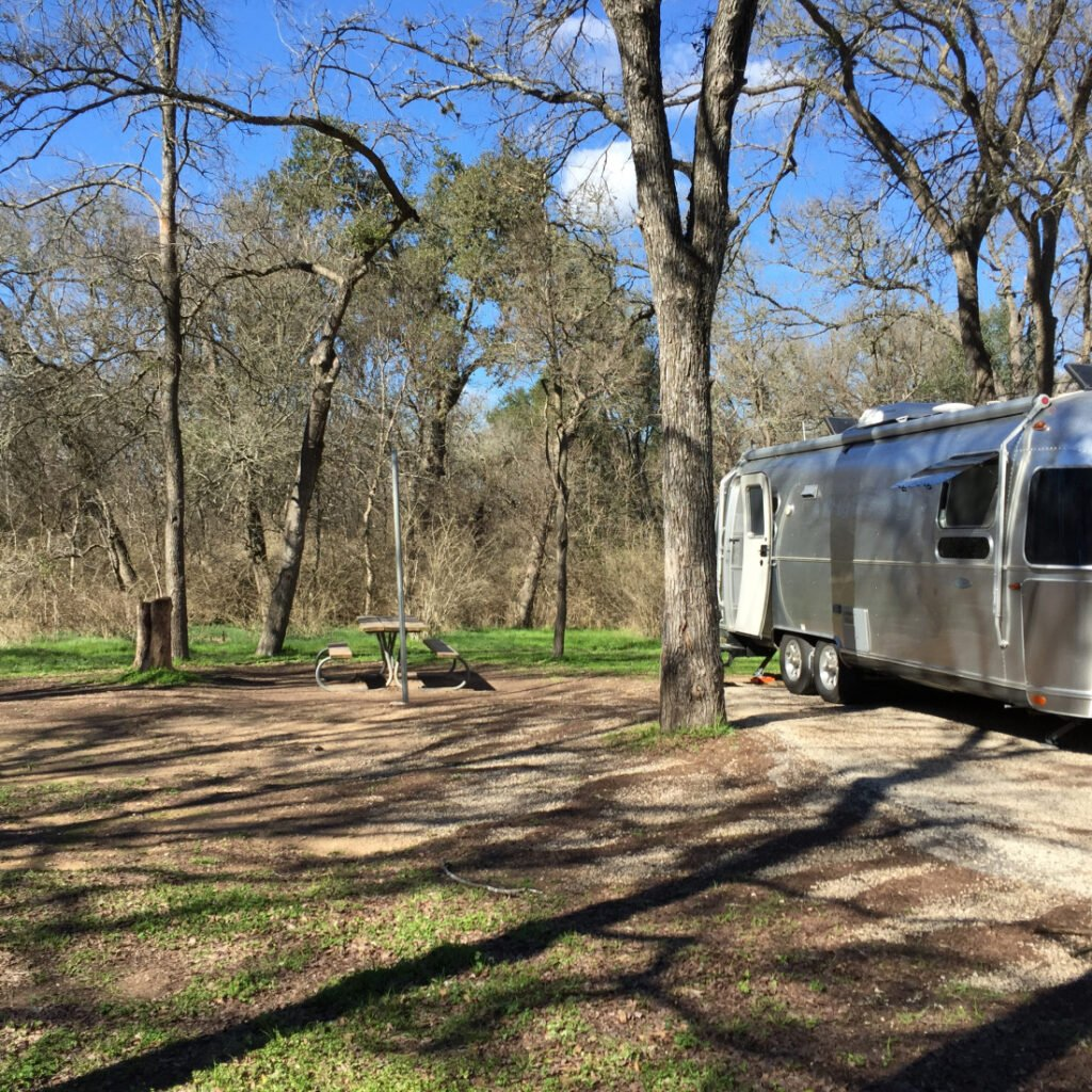 Silver airstream parked in a gravel spot with picnic table and trees around.