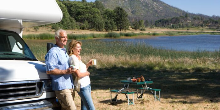 older couple outside of RV considering AARP discounts