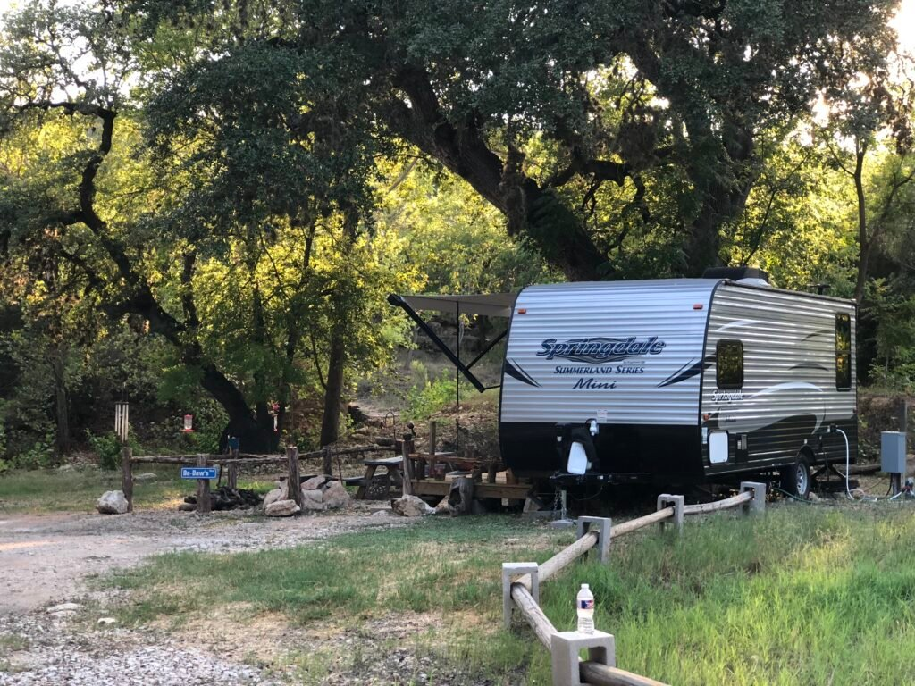small travel trailer in RV site under large shade trees with picnic table nearby