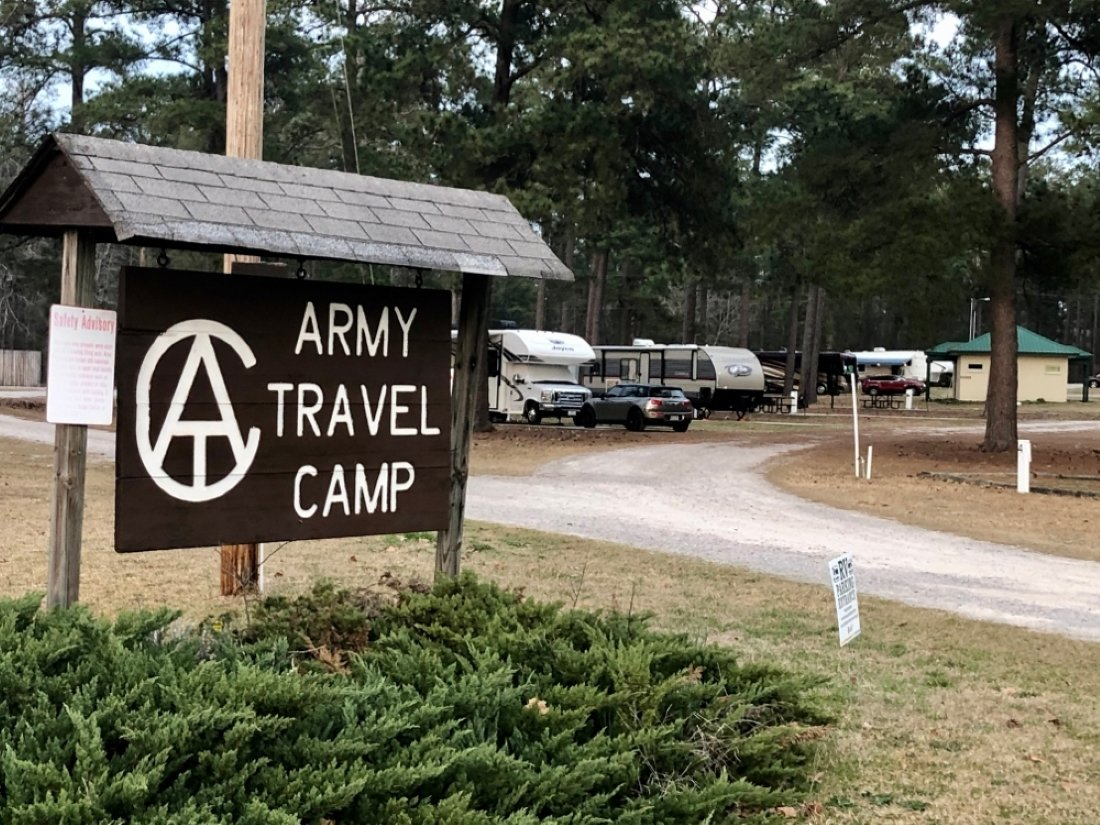 Welcome sign with RVs and tall trees in background
