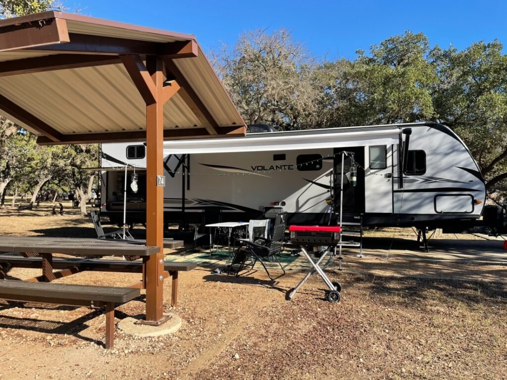 Covered picnic area beside travel trailer set up for camping