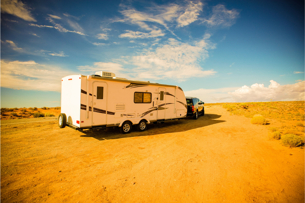 SUV towing a travel trailer down a dirt road - travel trailer advice for newbies