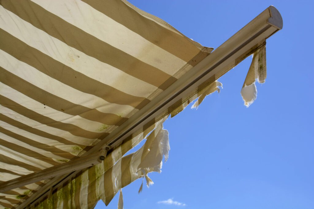 Ripped and dirty striped RV awning in front of blue summer sky