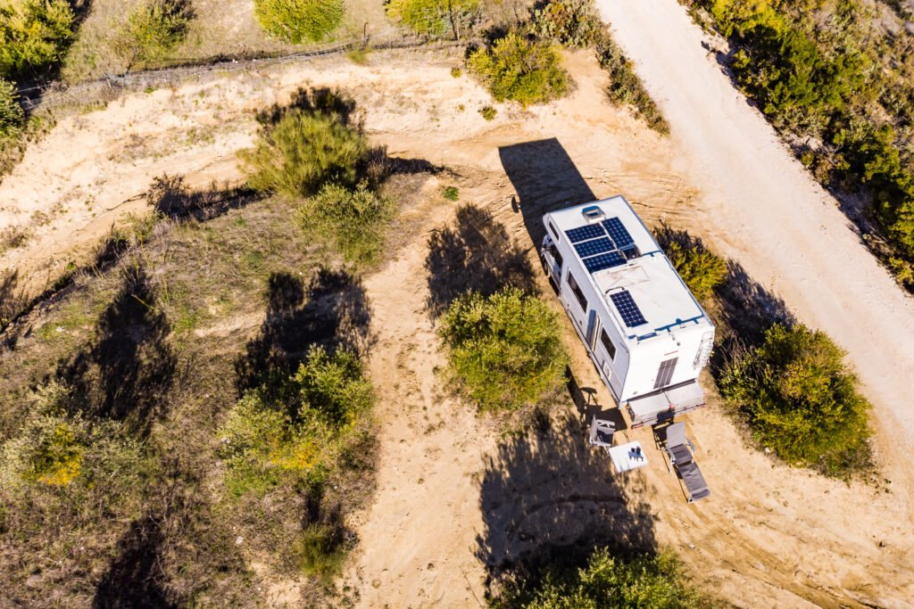 RV with solar panels in sparse land viewed from above.