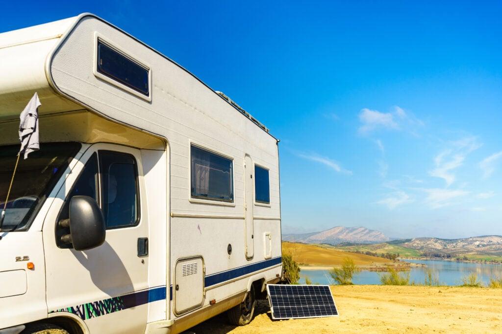 Portable RV solar panel leans against a class C motorhome